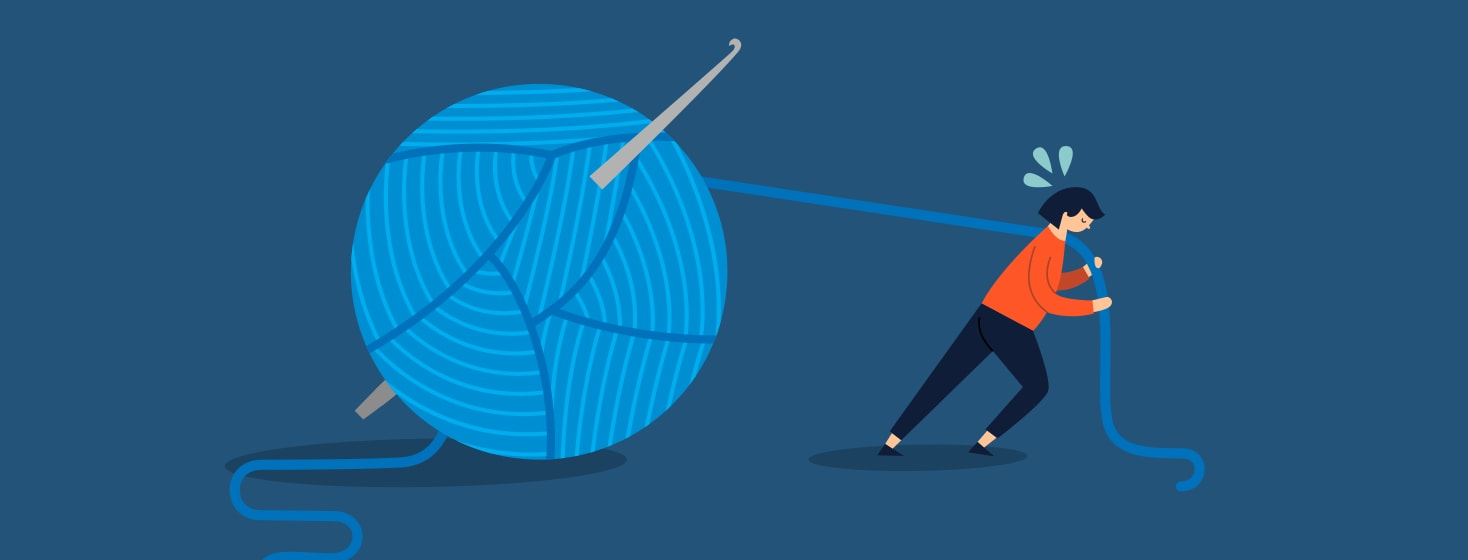 Woman struggling to drag a large ball of yarn along behind her