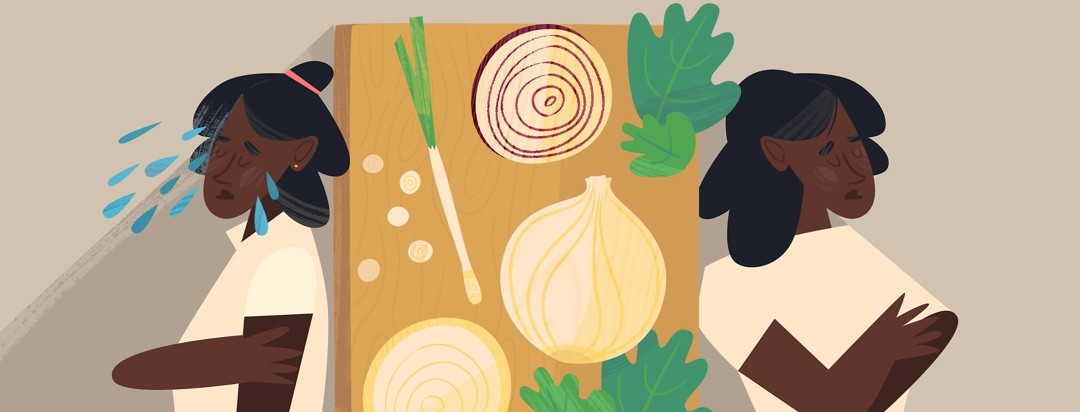 Two women looking upset on either side of a cutting board with onions on it