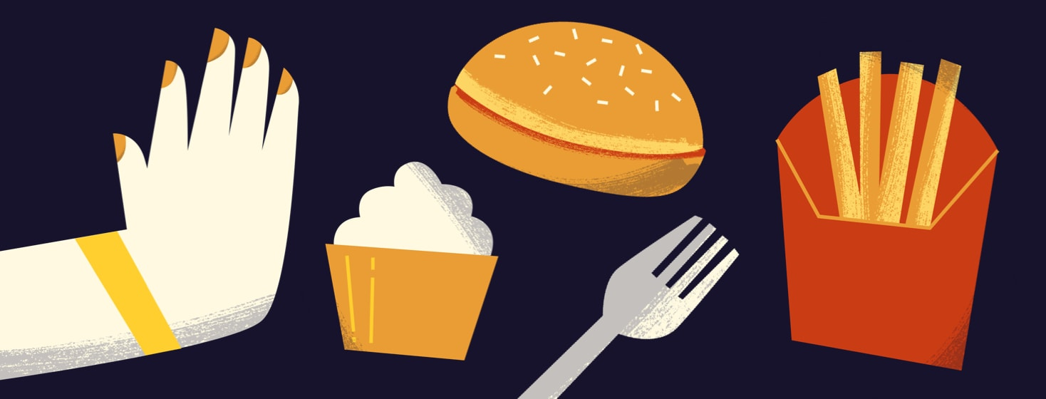 Hand pushing away sugar-heavy foods like a hamburger bun, fries, and a cupcake