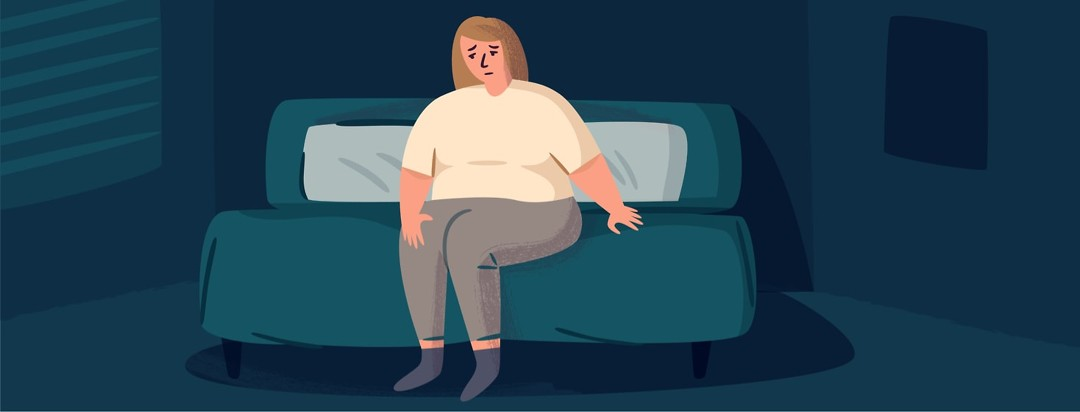 Woman sitting on the edge of her bed looking distressed
