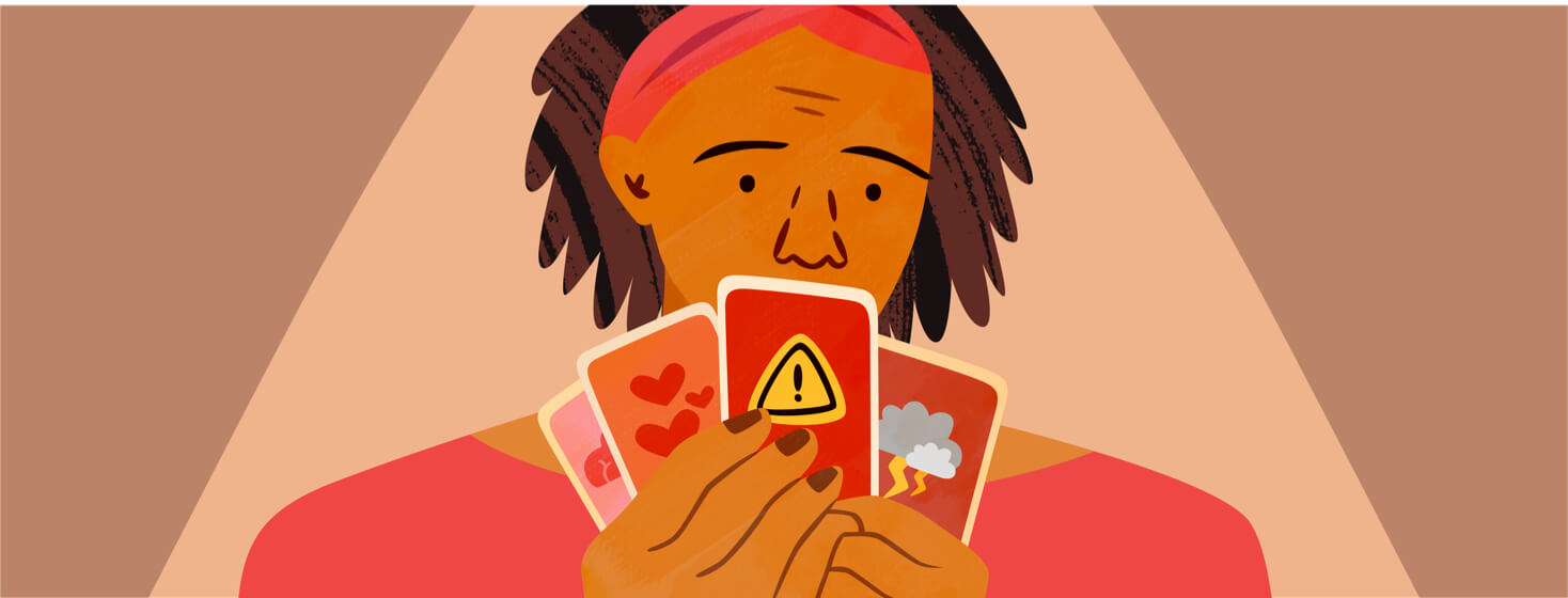 Woman holding up playing cards with different symbols of her emotional state on them